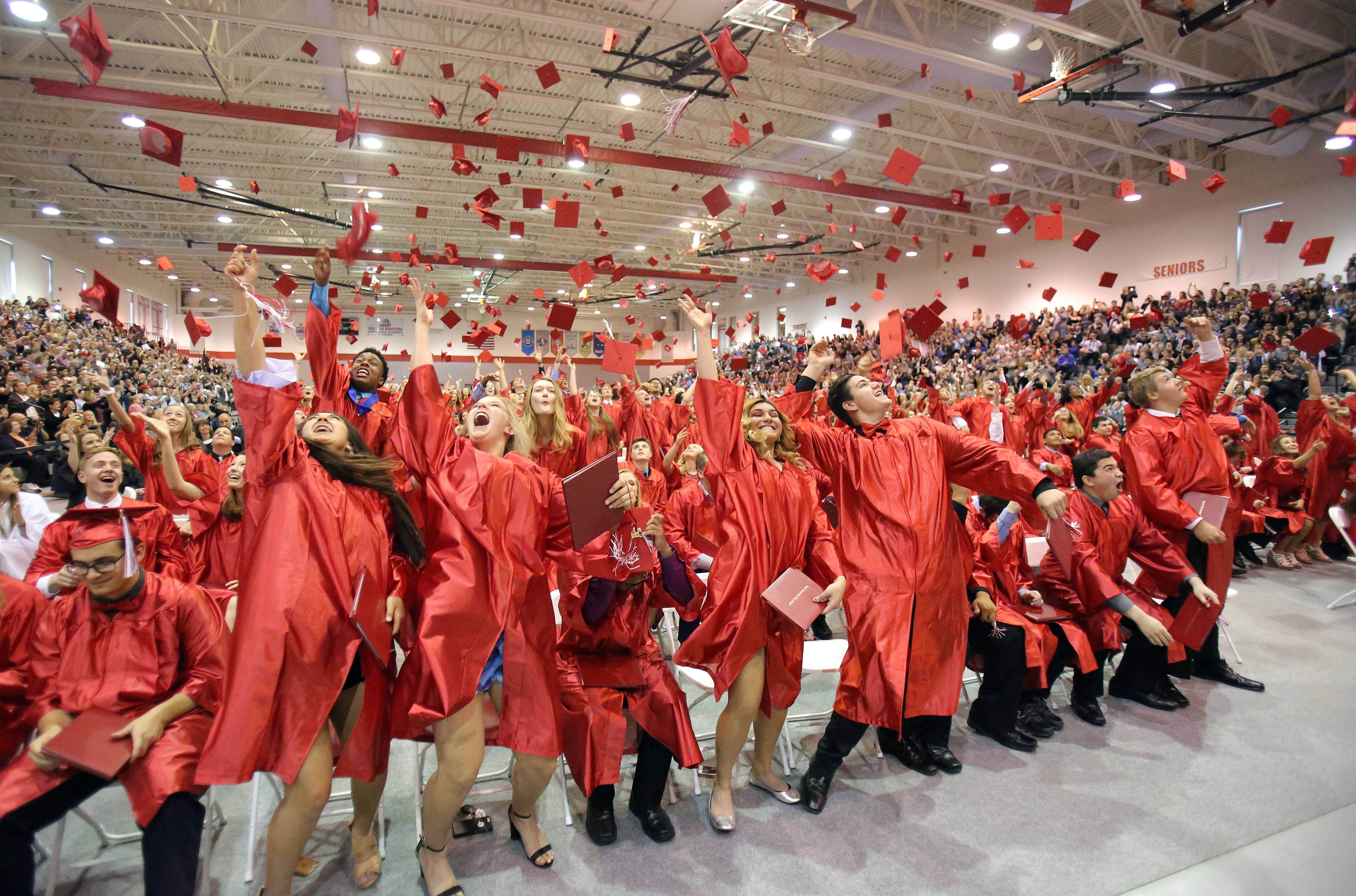 Graduates toss their caps during Grant High School's commencement ceremony Sunday in Fox Lake.