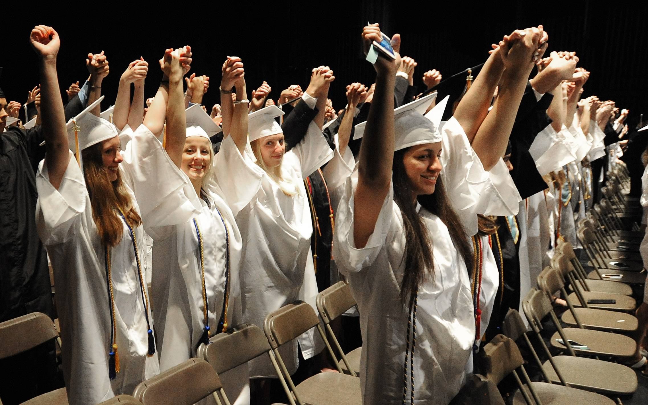 Maine West graduates of over 400 raise their hands in unity as the song Unity played at their commencement in the Rosemont Theatre on Sunday.