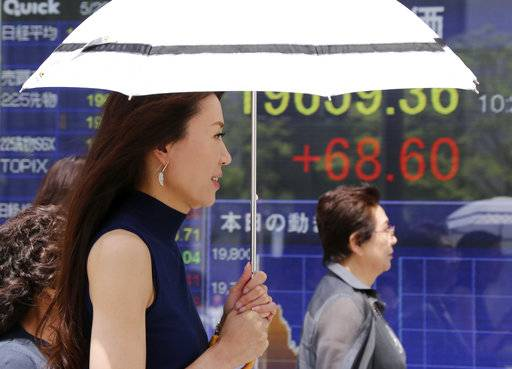 People walk by an electronic stock board of a securities firm in Tokyo, Monday, May 22, 2017. Asian stocks rose Monday, cheered by the latest rally on Wall Street and relative quiet in U.S. politics as President Donald Trump began his first official trip overseas as president. (AP Photo/Koji Sasahara)