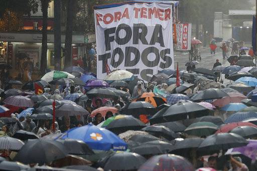 "Demonstrators march against Brazil's President Michel Temer, holding a banner that reads in Portuguese ""Temer Out"" and ""Out with everybody,"" in Sao Paulo, Brazil, Sunday, May 21, 2017. Temer has been under siege since the newspaper O Globo reported last week that he was recorded endorsing hush money for a former lawmaker who has been jailed for graft. (AP Photo/Andre Penner)"