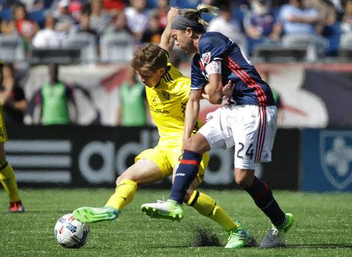 Columbus Crew midfielder Will Trapp, left, and New England Revolution midfielder Lee Nguyen, right, pursue the ball during the second half of an MLS soccer game, Sunday, May 21, 2017, in Foxborough, Mass. The Revolution won 2-1. (AP Photo/Steven Senne)