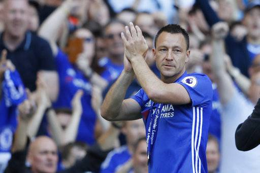 Chelsea captain John Terry applauds the fans wearing his winners medal after they won the league, following the English Premier League soccer match between Chelsea and Sunderland at Stamford Bridge stadium in London, Sunday, May 21, 2017. (AP Photo/Frank Augstein)