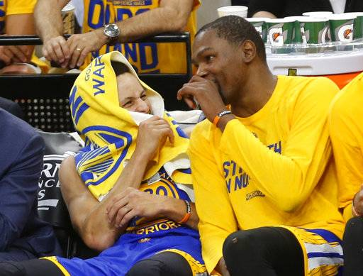 In closing minutes of the game Golden State Warriors guard Stephen Curry (30) laughs with Golden State Warriors forward Kevin Durant (35) in Game 3 of the NBA basketball Western Conference finals on Saturday, May 20, 2017, in San Antonio. (AP Photo/Ronald Cortes)