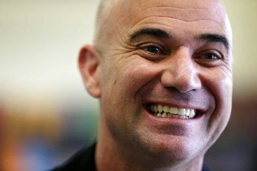 FILE - In this Wednesday, Sept. 24, 2014 file photo, Hall of Fame tennis player Andre Agassi smiles during a visit to University Heights Charter School, in Newark, N.J. Novak Djokovic has announced that Andre Agassi will coach him at the French Open, which starts Sunday, May 28, 2017. (AP Photo/Julio Cortez, File)