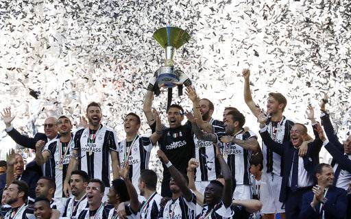 Juventus goalkeeper Gianluigi Buffon lifts the trophy as Juventus players celebrate winning an unprecedented sixth consecutive Italian title, at the end of the Serie A soccer match between Juventus and Crotone at the Juventus stadium, in Turin, Italy, Sunday, May 21, 2017. (AP Photo/Antonio Calanni)