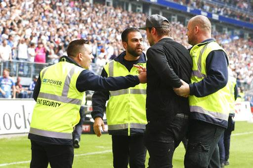 In this May 20, 2017 photo, Hamburg's Pierre-Michel Lasogga, second from right, being escorted out of the field after celebrating the 2-1 victory goal during the German Bundesliga soccer match between Hamburger SV and VfL Wolfsburg in the Volkspark Stadium in Hamburg,, Germany. Hamburg forward Pierre-Michel Lasogga wanted to celebrate with teammates when they scored a vital goal to clinch survival on the final day of the German league season on Saturday. But one steward didn't recognize Lasogga and strong-armed the 25-year-old player back off the field, despite the forward's protests that he was a Hamburg player. (Christian Charisius/dpa via AP)