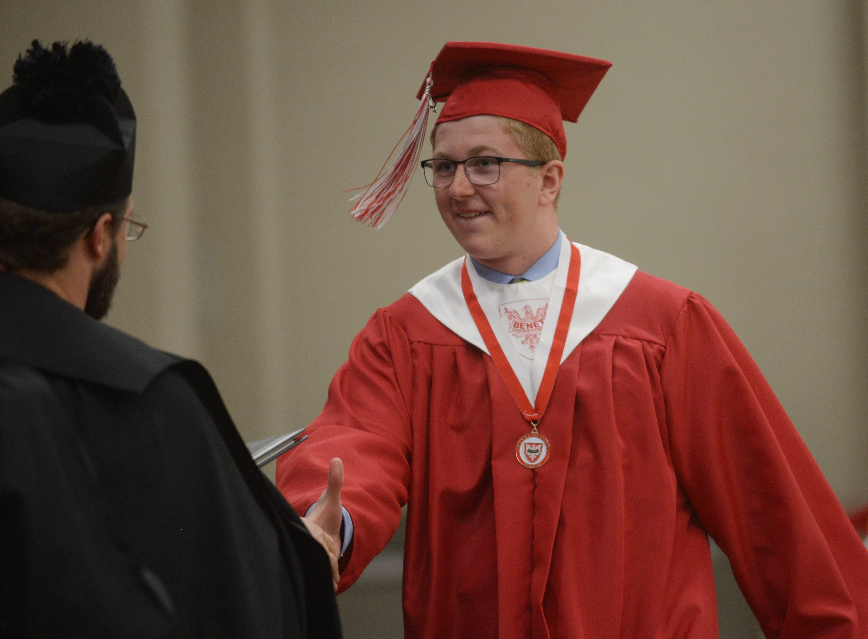 Student Government President Max Tuttle receives his diploma from Rt. Rev. Austin Murphy, O. S. B during the Benet Academy graduation in Lisle Sunday.