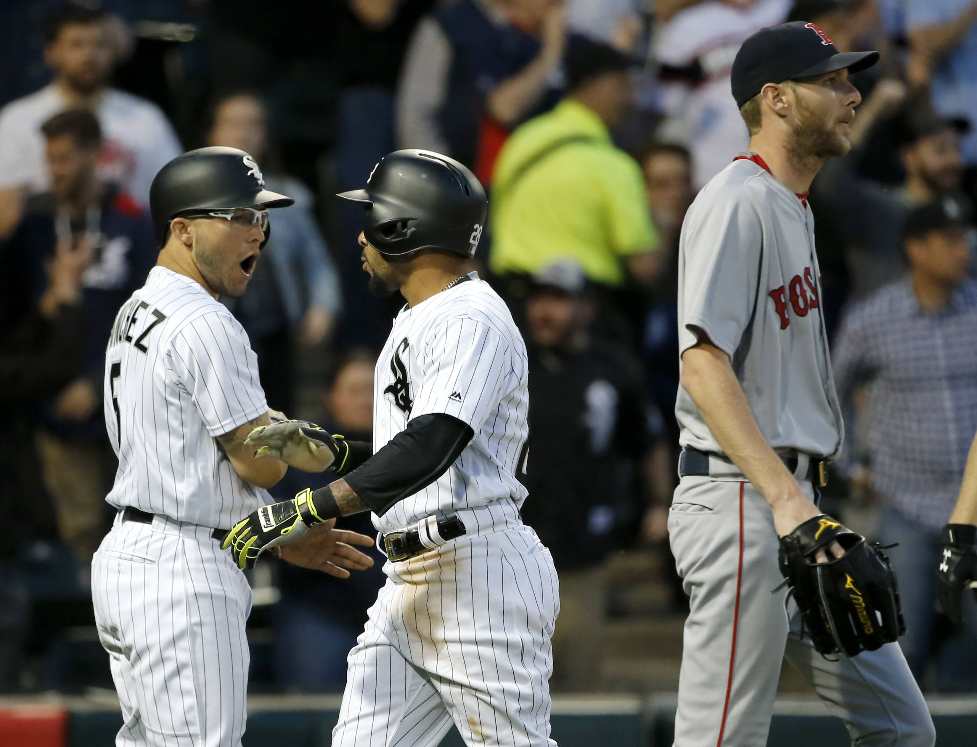 Chicago White Sox's Yolmer Sanchez, left, and Leury Garcia, center, celebrate after scoring on a single by Jose Abreu, off a pitch from Boston Red Sox starting pitcher Chris Sale, right, during the second inning of a baseball game Tuesday, May 30, 2017, in Chicago. (AP Photo/Charles Rex Arbogast)