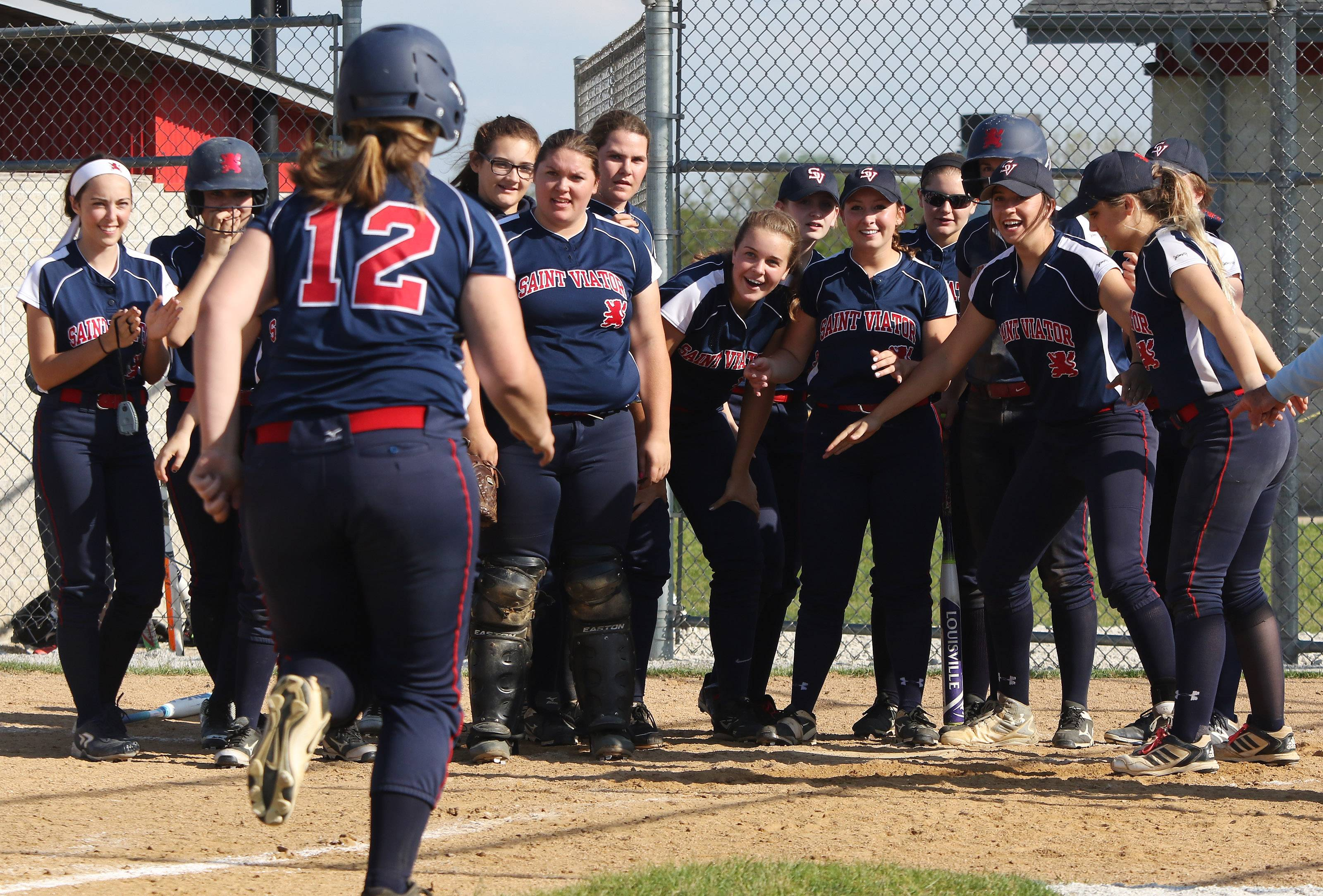 St. Viator teammates wait at the plate to celebrate with Cece Kaiser after she hit a 2-run homer in the fourth inning of Class 3A sectional semifinal play at Antioch on Tuesday.