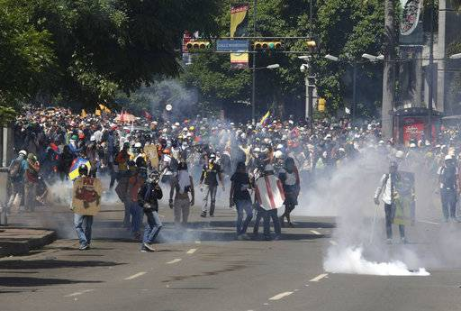 Demonstrators get ready to confront security forces during anti-government protests in Caracas, Venezuela, Tuesday, May 30, 2017. Protests against Maduro's government have left dozens dead in the last two months. The opposition wants immediate presidential elections and the liberation of political prisoners.(AP Photo/Fernando Llano)