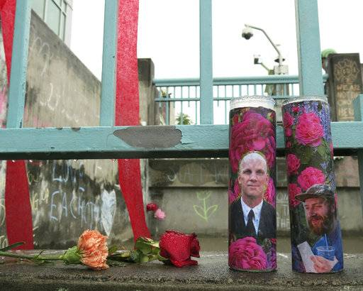 Votive candles bearing the photos of two men who were fatally stabbed on a Portland, Ore., light-train while trying to stop another man from harassing two young women with an anti-Muslim tirade, sit on a rain-soaked memorial on Tuesday, May 30, 2107 in Portland. Taliesin Myrddin Namkai-Meche, 23, and Ricky Best, 53, died in the attack. The suspect, Jeremy Joseph Christian, 35, made a first court appearance on charges of aggravated murder and attempted murder Tuesday in a Portland, Oregon courthouse. (AP Photo/Gillian Flaccus)