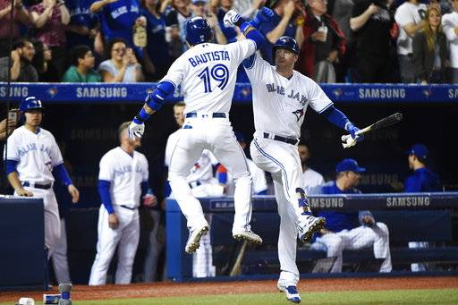 Toronto Blue Jays right fielder Jose Bautista (19) celebrates his solo home run against the Cincinnati Reds with Justin Smoak (14) during the fourth inning of an interleague baseball game in Toronto on Tuesday, May 30, 2017. (Nathan Denette/The Canadian Press via AP)