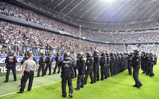 Police officers and orderlies secure the pitch at the 80th minute after Munich fans started to riot during the first half of the German Bundesliga 2nd division relegation soccer match between TSV'1860 Munich and Jahn Regensburg in the Allianz Arena in Munich, Germany, Tuesday, May 30, 2017. Former Bundesliga champion 1860 Munich was relegated from Germany's second division in a game that was held up for 15 minutes toward the end because of violence from its angry fans. (Peter Kneffel/dpa via AP)