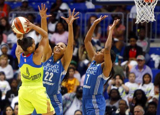FILE - In this Saturday, May 20, 2017, file photo, Dallas Wings guard Skylar Diggins (4) shoots as Minnesota Lynx forward Plenette Pierson (22) and guard Jia Perkins (7) defends in the third quarter of a WNBA basketball game in Arlington, Texas. Minnesota finished May unbeaten again, moving up to the spot in The Associated Press WNBA power poll. Next up is a game against No. 2 Seattle on Saturday. (Rose Baca/The Dallas Morning News via AP, File)