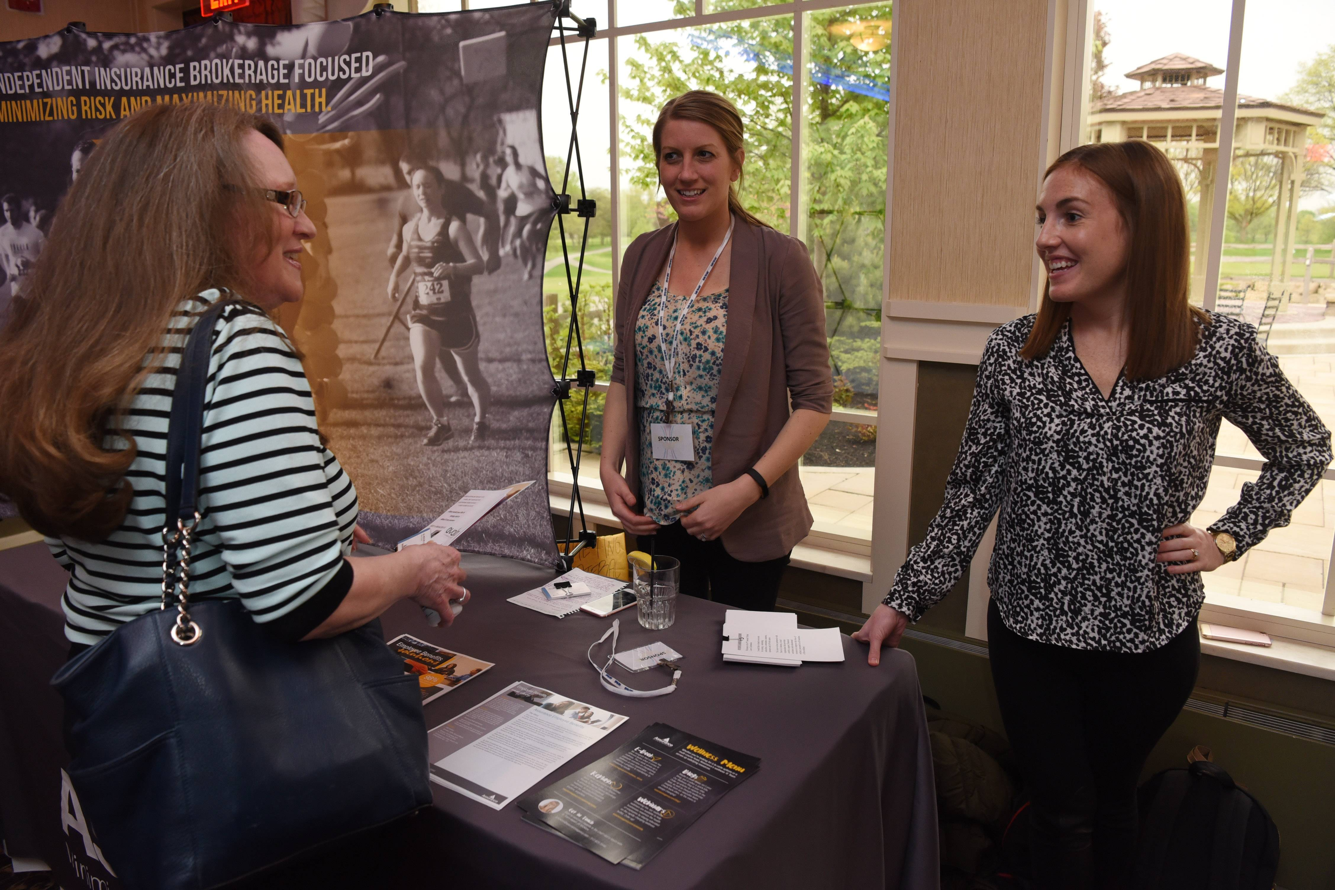 Laura Holze of Elgin, left, visits with Jill Micklow, middle and Megan Nester at the Assurance table during the finale of the Fittest Loser competition, held at Chandler's Banquets in Schaumburg Tuesday.