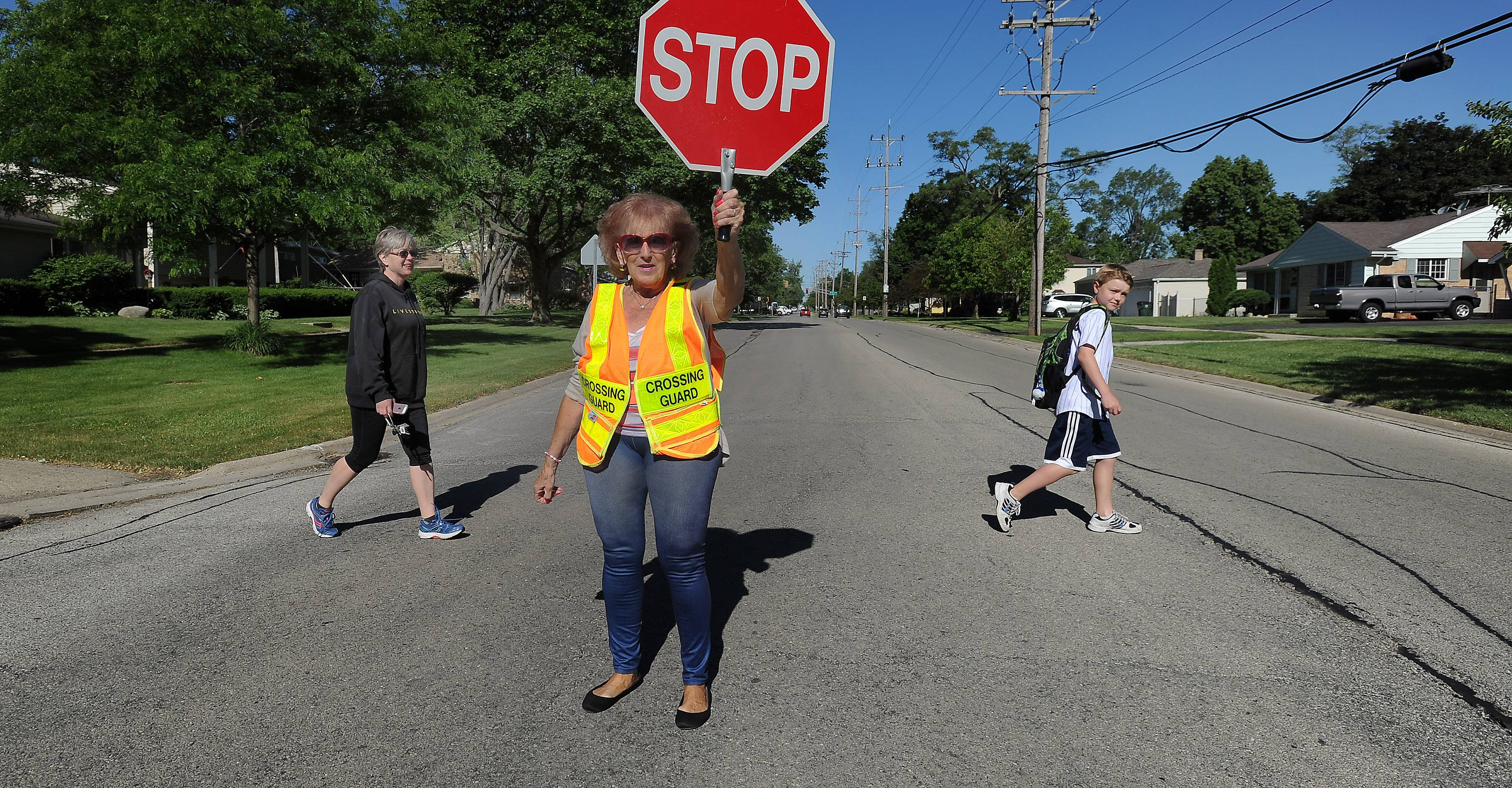 Lois Wardecki, of Wheeling stops all traffic as Daniel Thielen, 10, and his mom Laura of Arlington Heights, cross the road safely as he ventures off to school in the morning. Wardecki is retiring after two decades as a crossing guard helping students get to Olive-Mary Stitt Elementary and St. James schools.