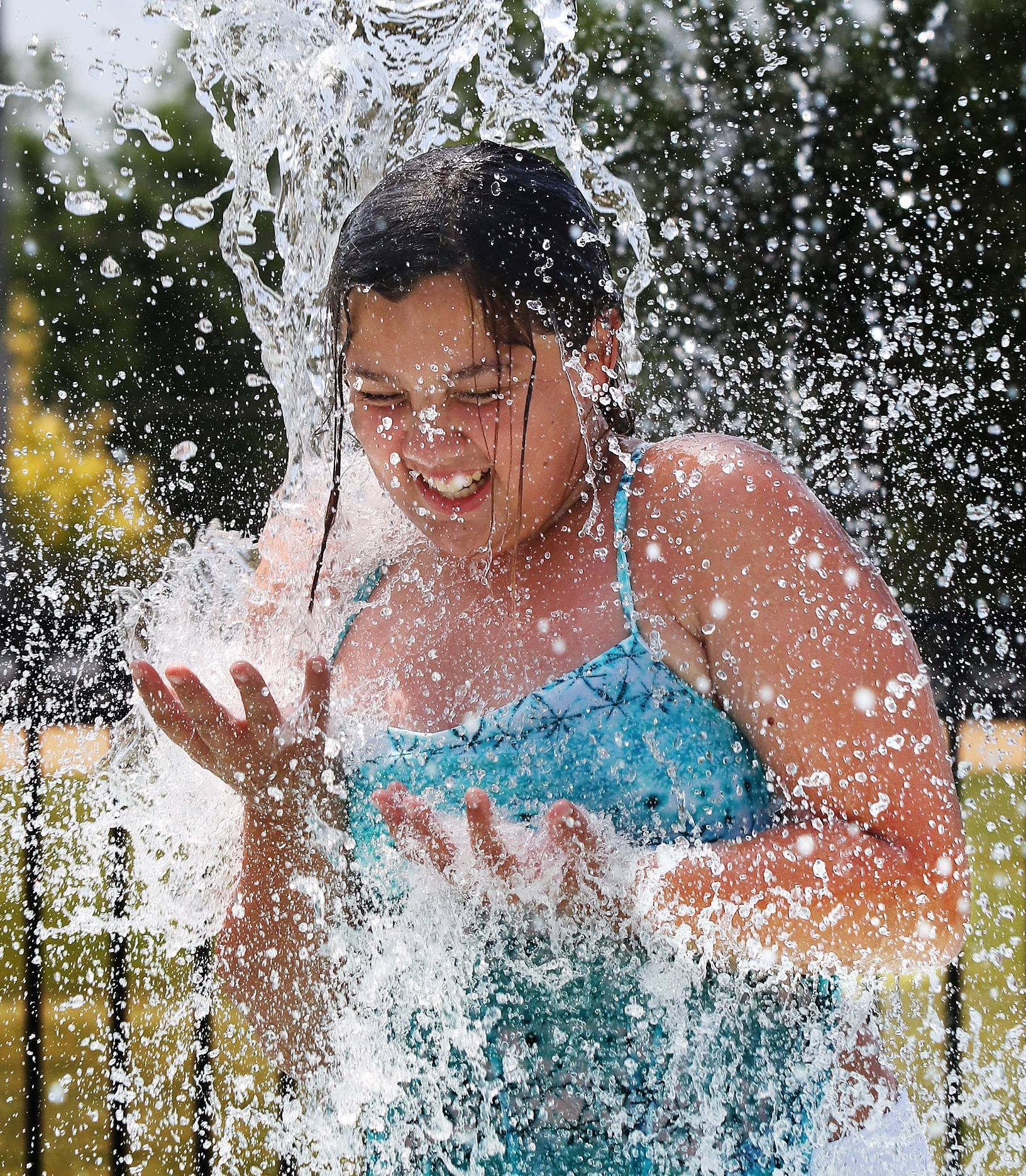 Isabella Adkins, 12, of Grayslake has a bucket of water wash over her as she joins children playing at the Grayslake Park District Spray Park on Tuesday. The cool water made for refreshing play on the hot summer day.