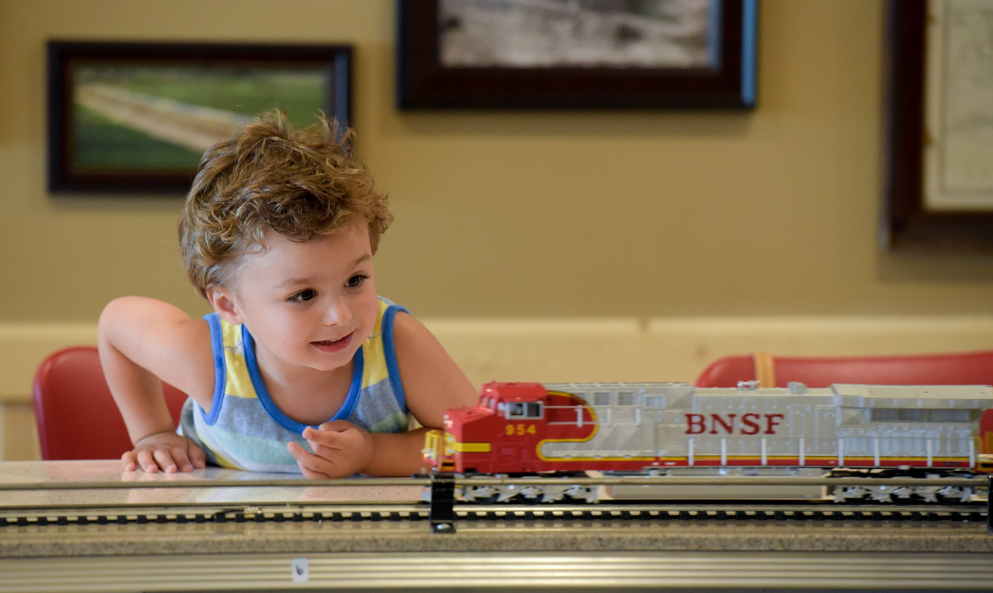 Vinny Barbanente, 3, of Inverness, gets a close-up look at a Lionel model train Thursday as it rolls by delivering food to diners at 2Toots Train Whistle Grill in Naperville. The Naperville location of the family-friendly train-themed restaurant opened this spring.