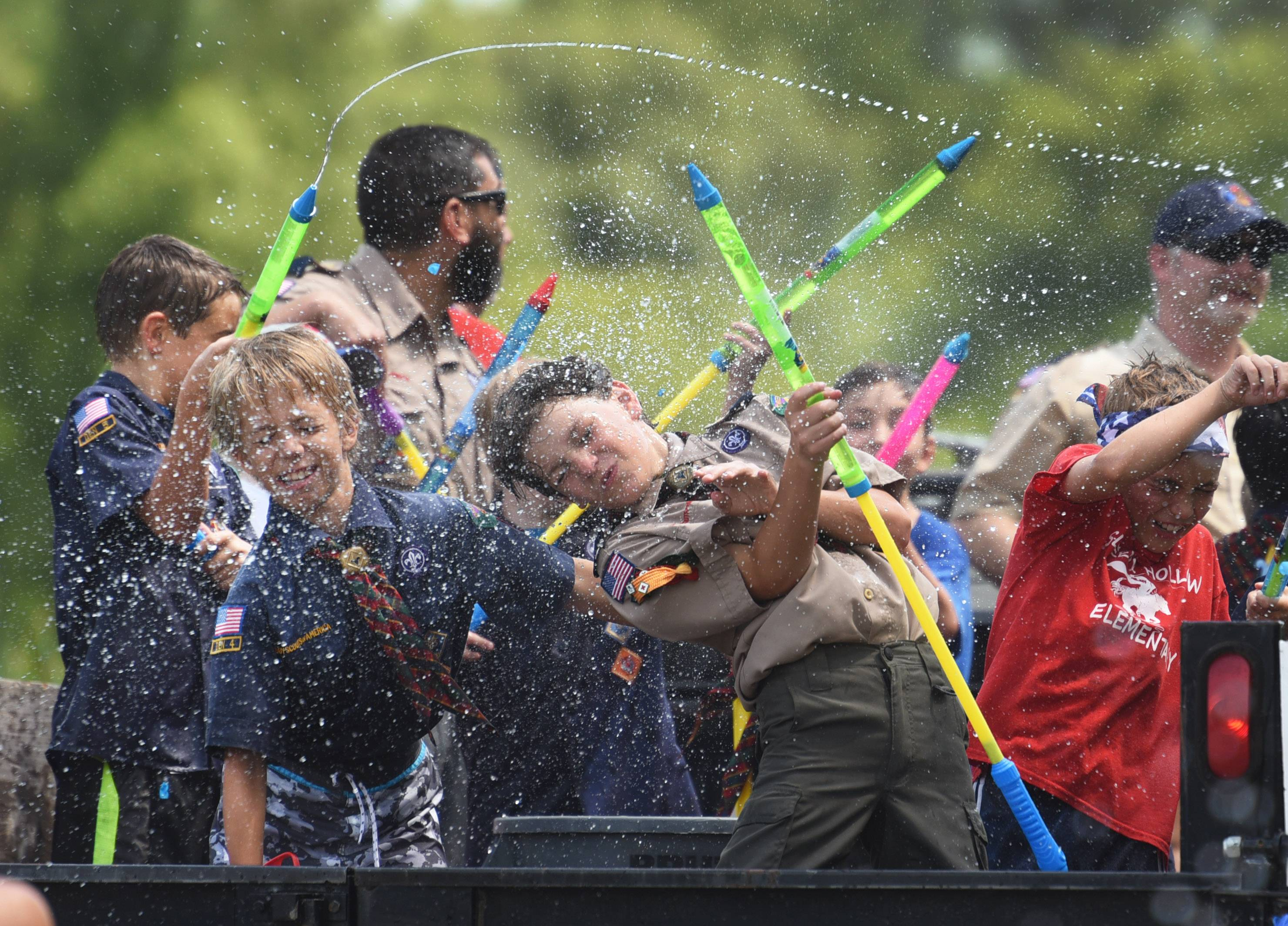 Members of the Sleepy Hollow Cub Scout Pack 88 Timmy Pribel, left, and Ian Bury, center, get hit with a water balloon during a battle between paradegoers and the scouts during Tuesday's Bill Ritchie Memorial Parade in Sleepy Hollow.