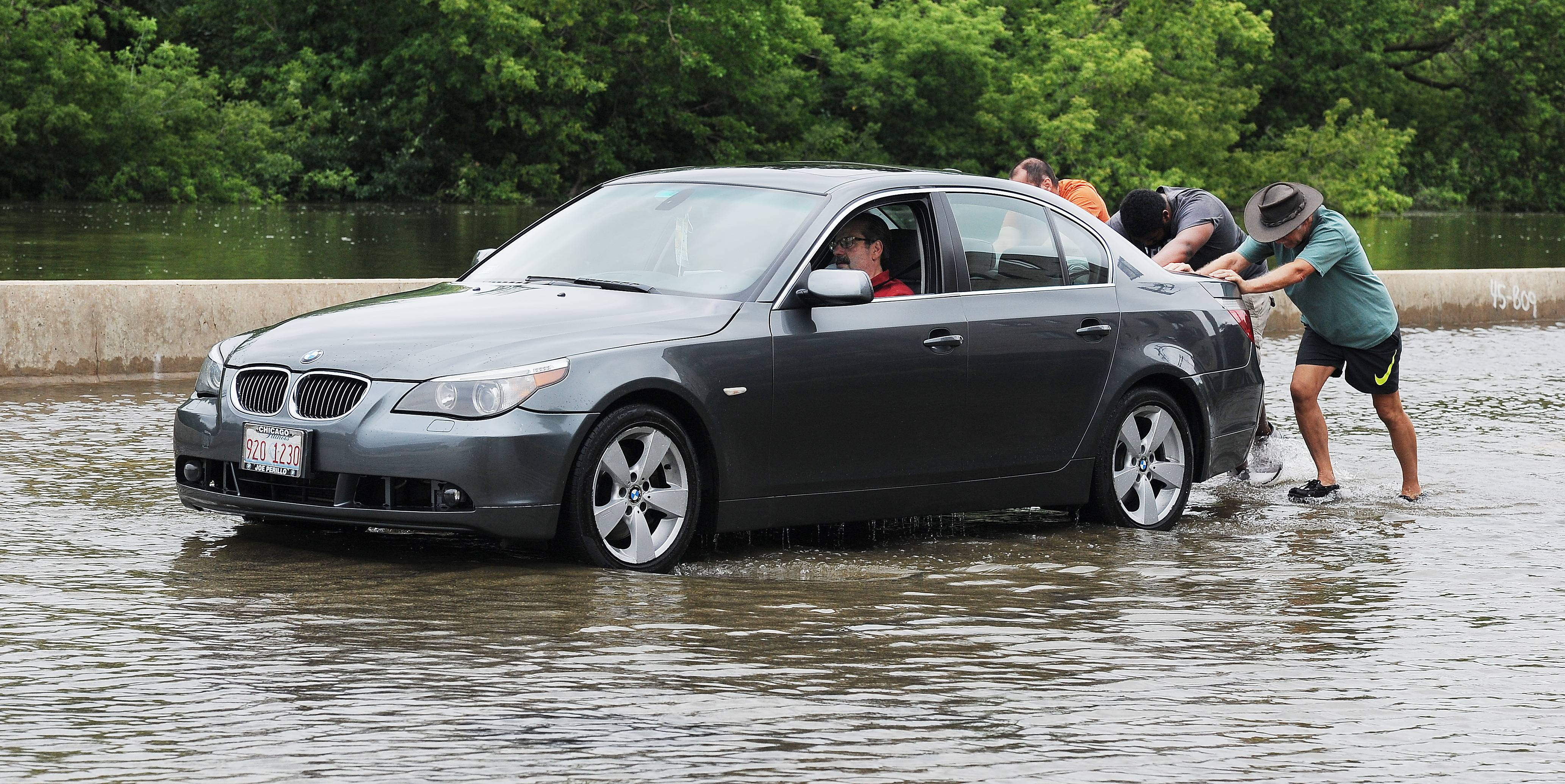 Galen Hiestand as well as Jacob and Mike Herz lend a helping hand to push the stalled car of Tom Bonanno out of the water on River Road in Des Plaines after he drove through it trying to get to his son's house.