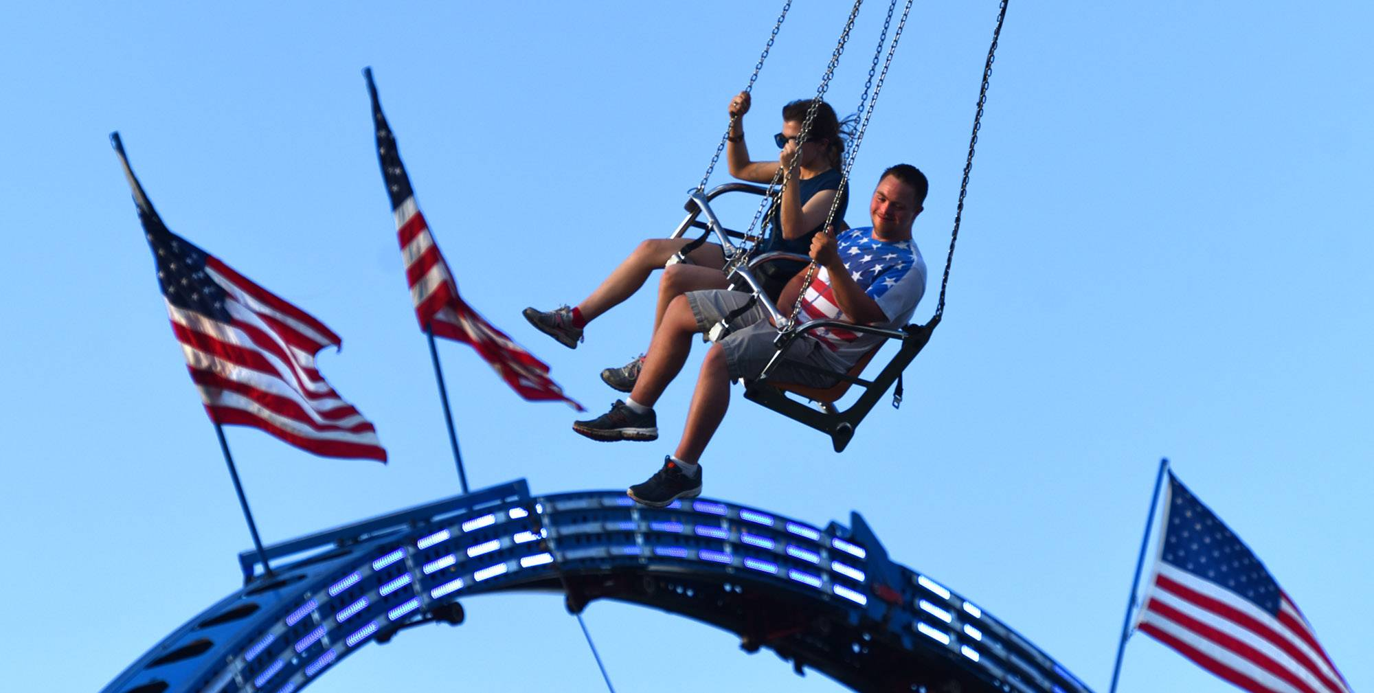 A man wearing a patriotic shirt swings past American Flags as he rides the Sky Ryder at Vernion Hills Summer Celebraton in Century Park Thursday evening.