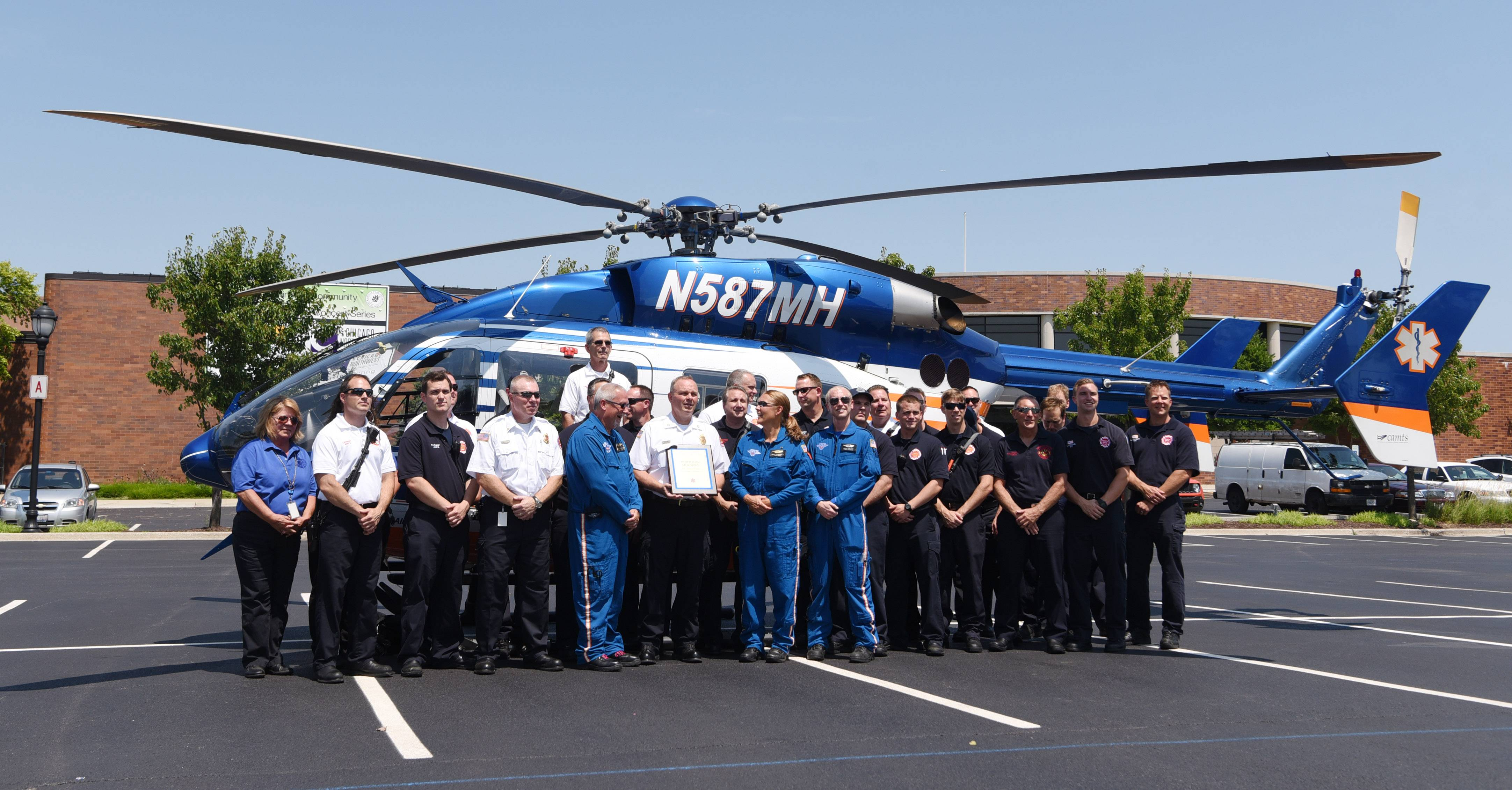 Members of the various departments involved in responding to a May 18, 2016, single-vehicle crash have their photo taken in front of the Flight For Life-McHenry Base helicopter prior to the presentation of the 23rd annual Scene Call of the Year Award to the Elk Grove Village Fire Department Thursday.