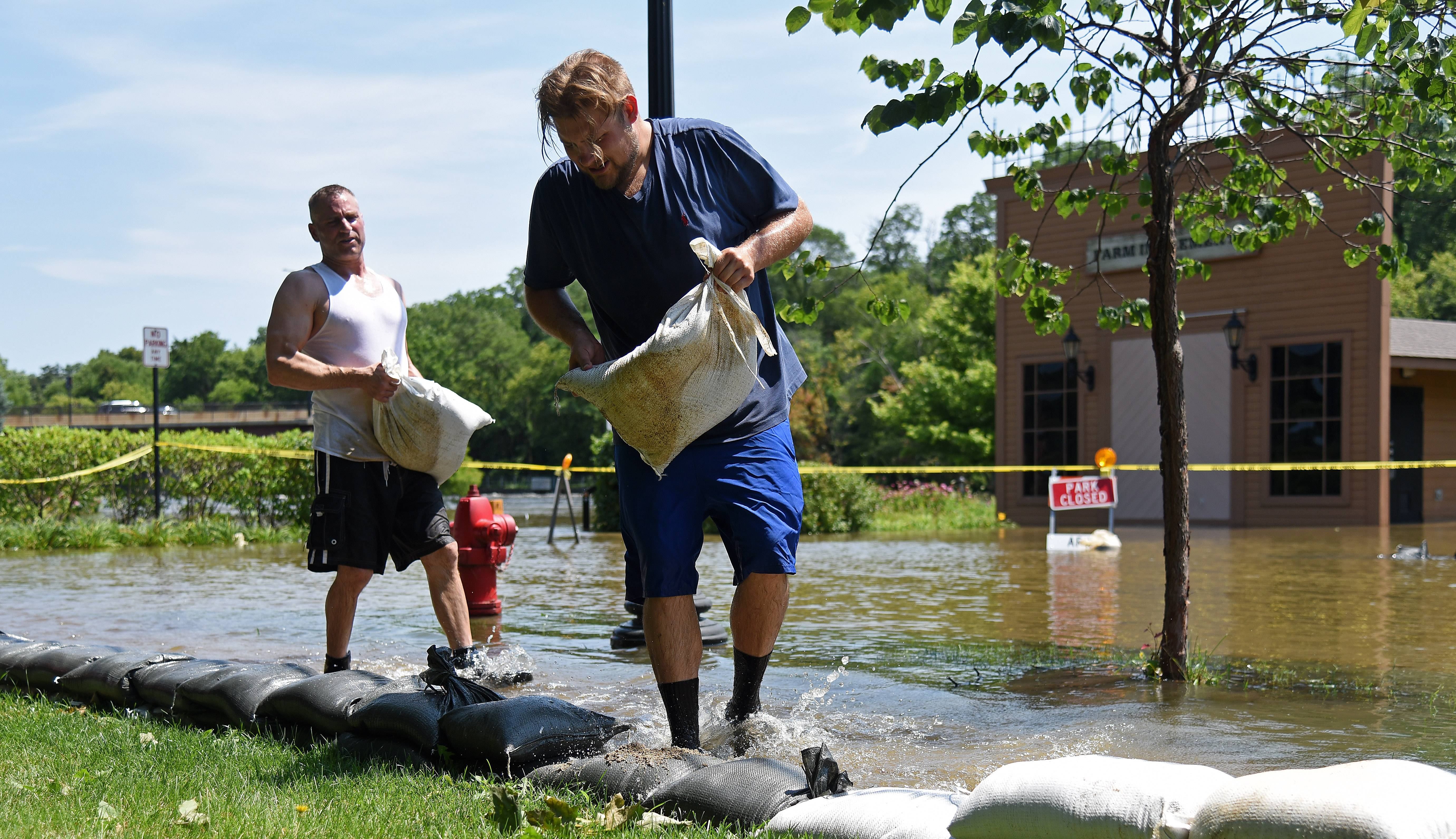 Tom McCleary, right, and Ray Robarge put another layer of sandbags on their way after Wednesday night's rain raised the water level to a new high point for the week on La Fox River Drive Thursday.