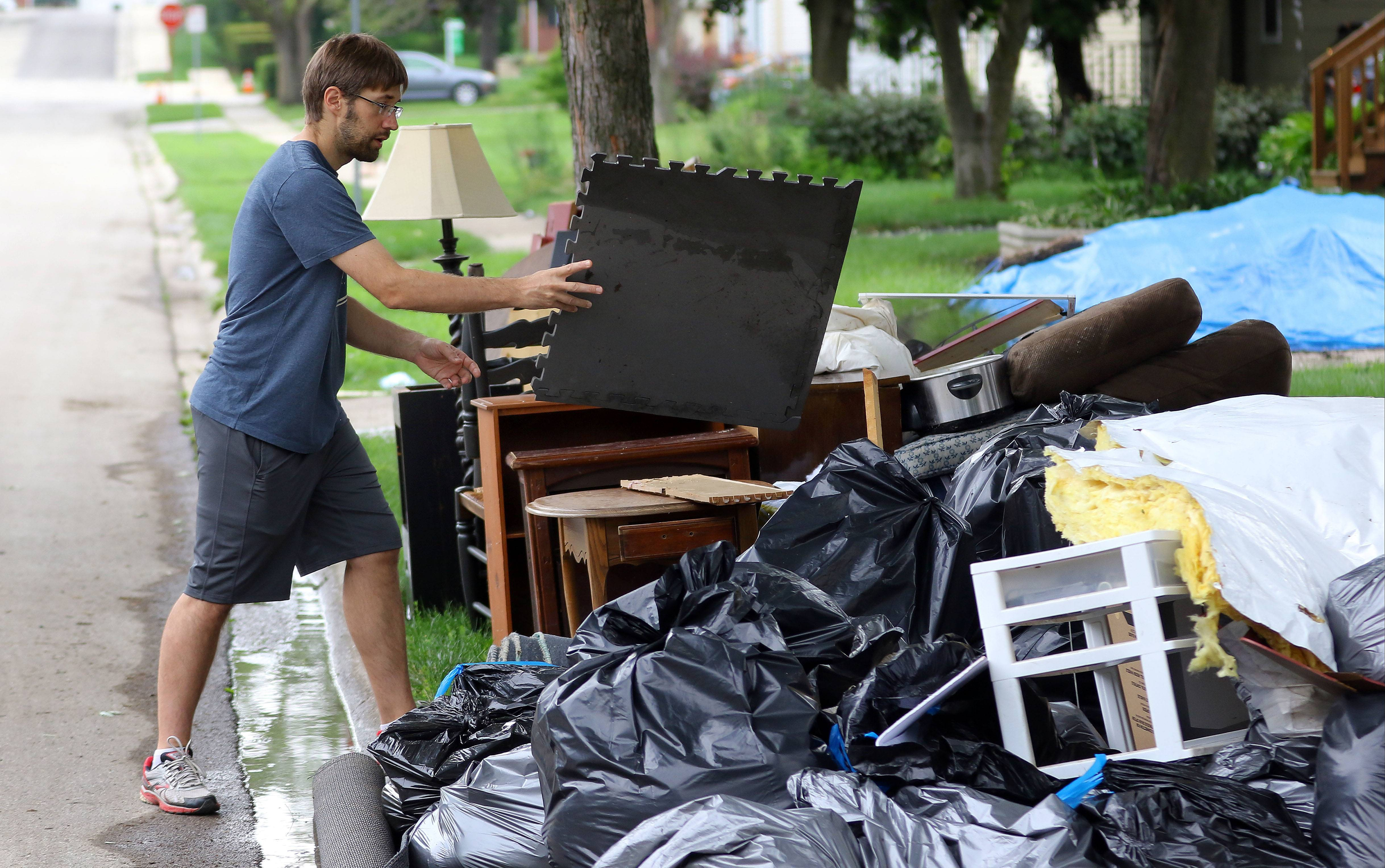 Chris Walter of Mundelein throws out flooded items from his basement last month. Village officials may hire consultants to study why parts of Mundelein flooded July 12 and how to prevent it from happening again.