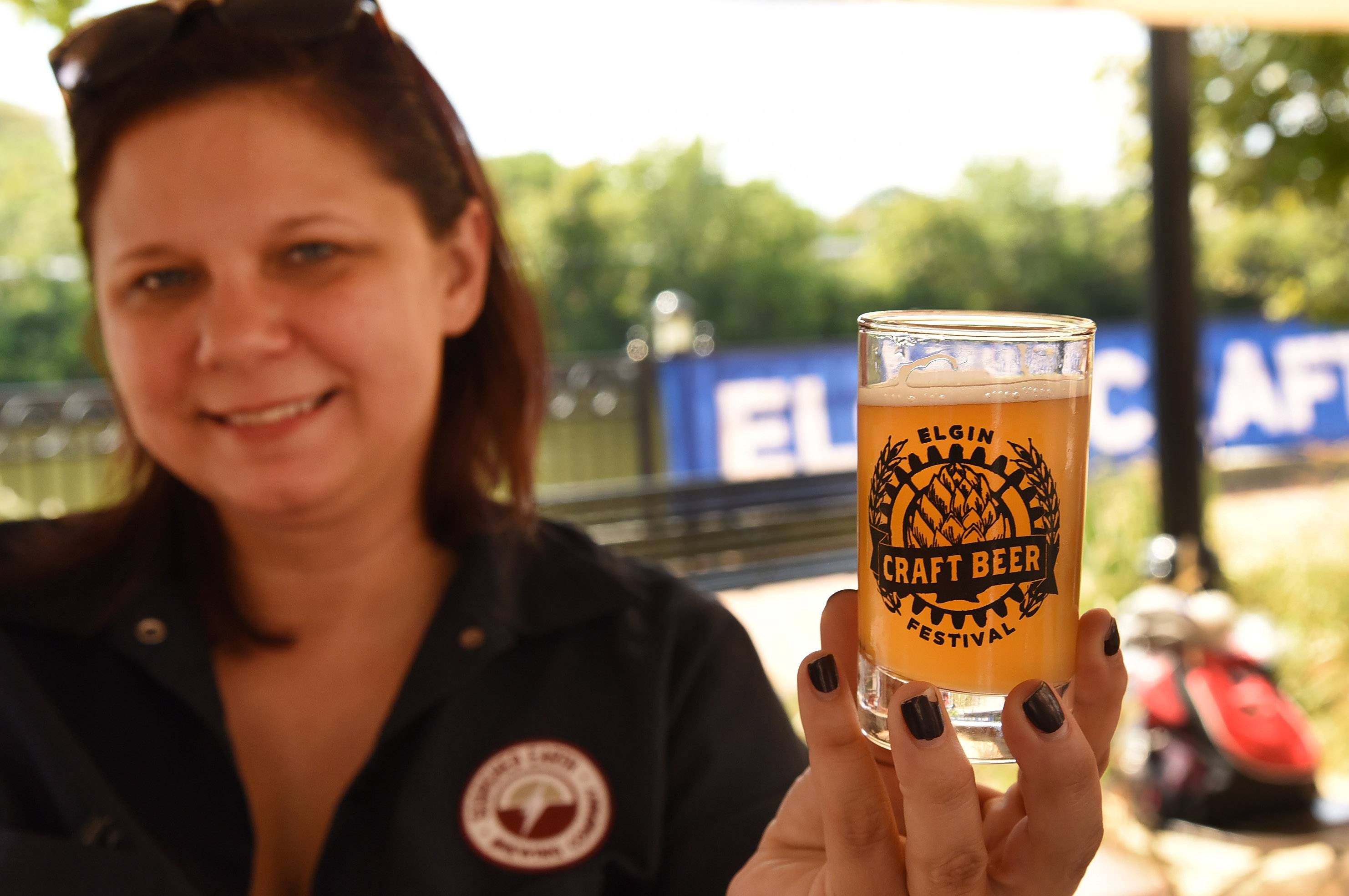 Megan Lange of Scorched Earth Brewery in Algonquin holds up one of its brews at the Elgin Craft Beer Festival Saturday.
