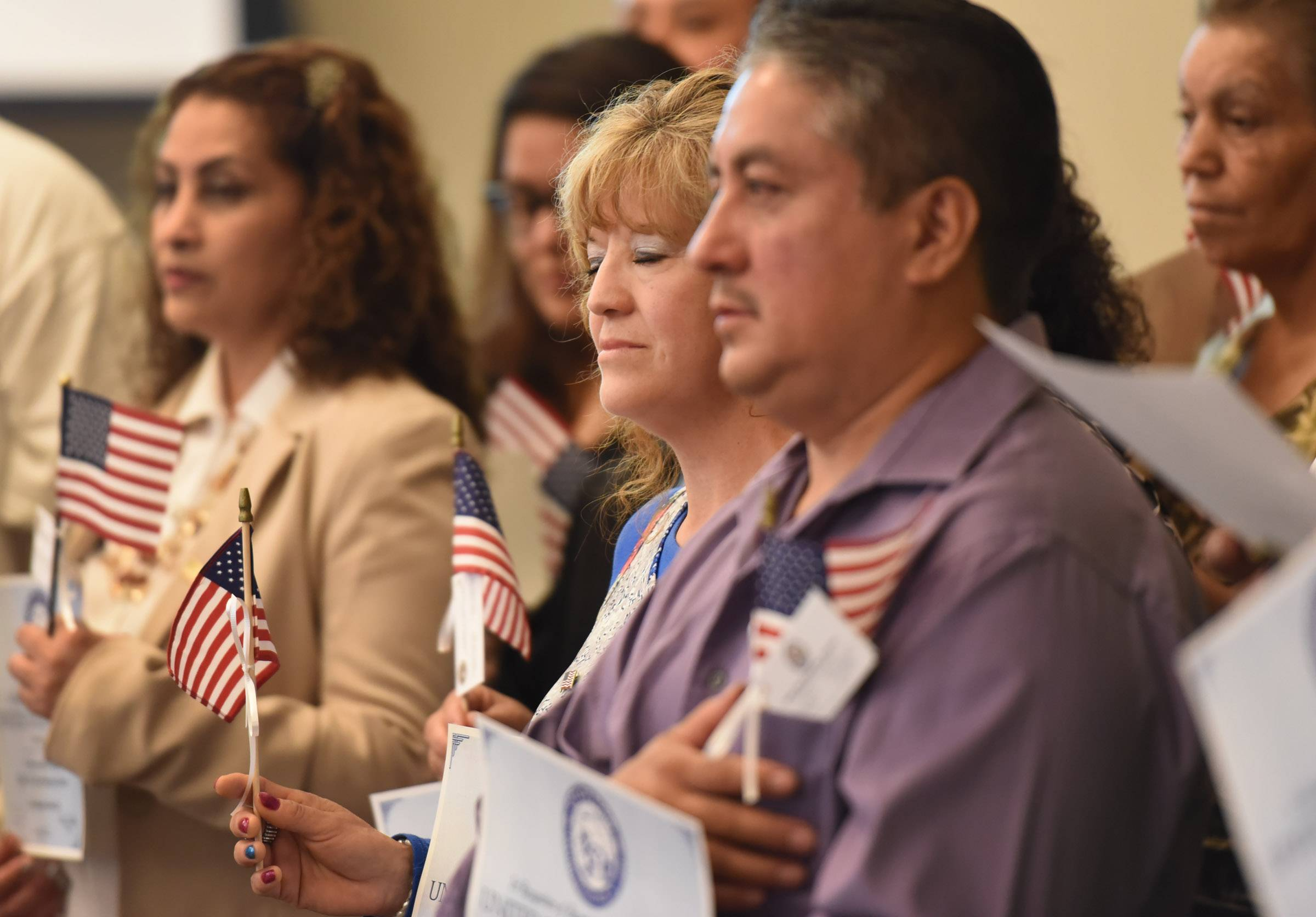 "Elvira Guillermina Marcial, center, closes her eyes as an Elgin choral group sings ""God Bless America"" at a recent citizenship recognition ceremony in Elgin."