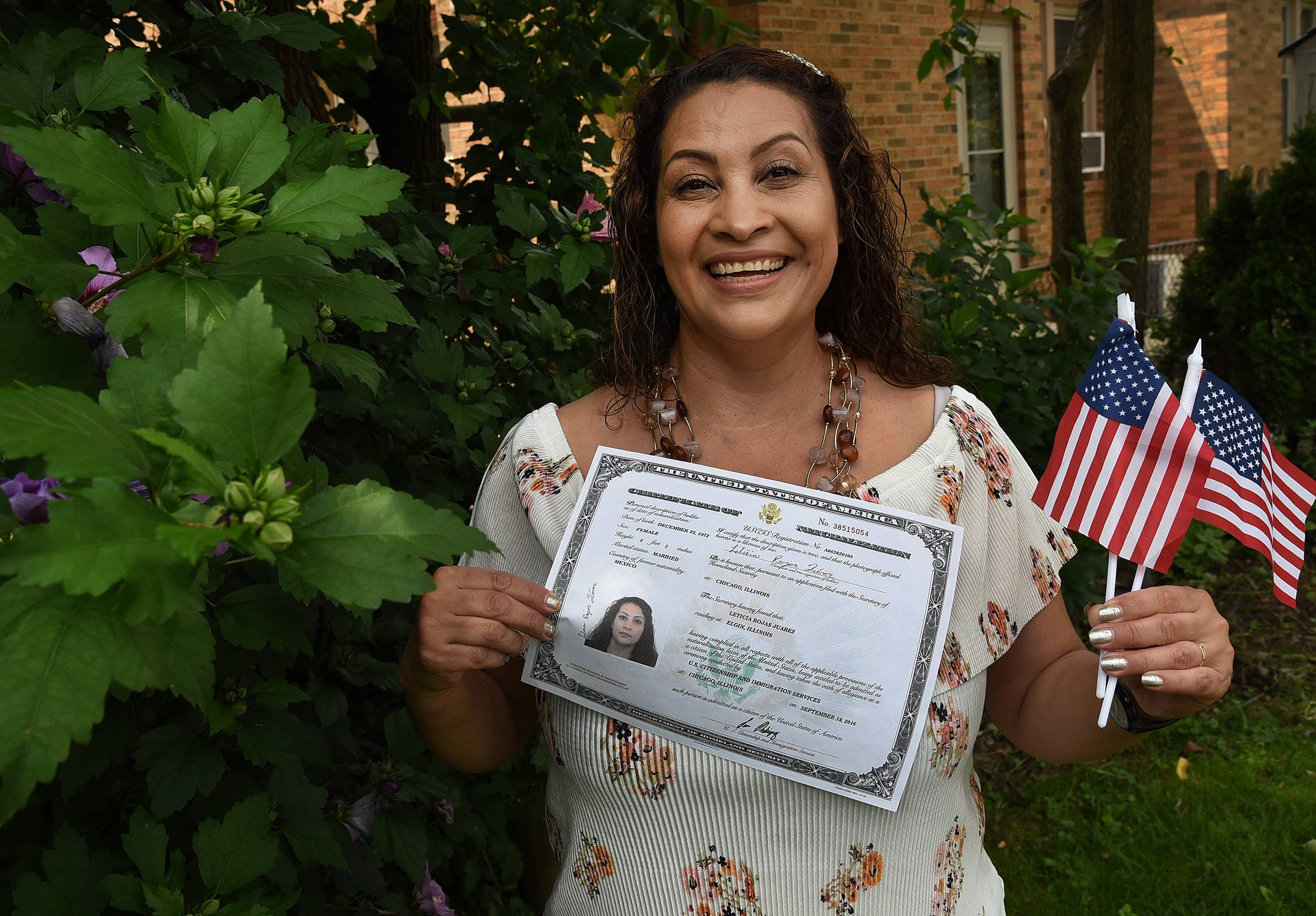 Leticia Rojas of Elgin became a U.S. citizen in September. Here she is in her backyard with her certificate of naturalization.