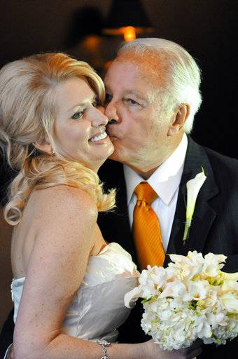 FILE - In this July 29, 2011 file photo, former Governor Edwin Edwards, right, kisses his new bride, Trina Grimes Scott, after a ceremony in the French Quarter in New Orleans, La. Louisiana's four-term former governor Edwards is having an ostentatious 90th birthday bash, Saturday, Aug. 12, 2017, with a $250-per-person price tag to attend. The powerful and charismatic Edwards was the dominant figure in Louisiana politics for decades before he went to federal prison for a corruption conviction. Out of prison for six years, he's got a wife five decades his junior, a 4-year-old son and continued popularity in his home state.