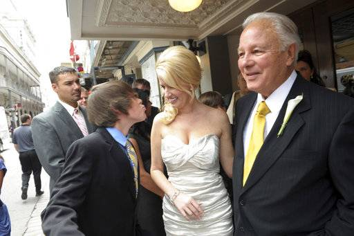 FILE - In this July 29, 2011 file photo, fourteen-year-old Logan Scott gets ready to kiss his mother Trina Grimes Scott, who married former Governor Edwin Edwards in the French Quarter in New Orleans, La. Louisiana's four-term former governor Edwards is having an ostentatious 90th birthday bash, Saturday, Aug. 12, 2017, with a $250-per-person price tag to attend. The powerful and charismatic Edwards was the dominant figure in Louisiana politics for decades before he went to federal prison for a corruption conviction. Out of prison for six years, he's got a wife five decades his junior, a 4-year-old son and continued popularity in his home state.