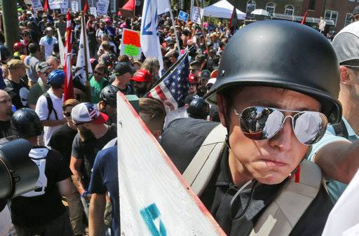A white nationalist demonstrator with a helmet and shield walks into Lee Park in Charlottesville, Va., Saturday, Aug. 12, 2017.   Hundreds of people chanted, threw punches, hurled water bottles and unleashed chemical sprays on each other Saturday after violence erupted at a white nationalist rally in Virginia. At least one person was arrested.