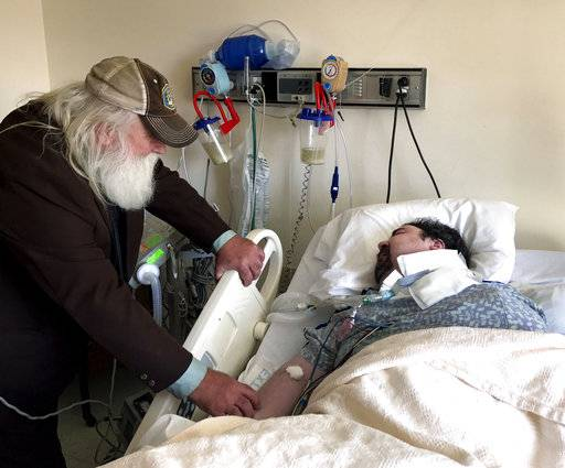 In this April 18, 2017, photo, Walter Wenger visits his severely disabled son, Steven, in a hospital in Kingston, N.Y, where he was moved after maggots were twice found in the area around his breathing tube while living in a state group home. The Associated Press obtained a confidential report on the state investigation that determined the 2016 infestations at the group home in Rome, N.Y., were the result of neglect by caregivers. In most states, details of abuse and neglect investigations in state-regulated institutions for the disabled are almost never made public.