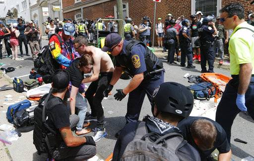 Rescue personnel help injured people after a car ran into a large group of protesters after a white nationalist rally in Charlottesville, Va., Saturday, Aug. 12, 2017. The nationalists were holding the rally to protest plans by the city of Charlottesville to remove a statue of Confederate Gen. Robert E. Lee. There were several hundred protesters marching in a long line when the car drove into a group of them.
