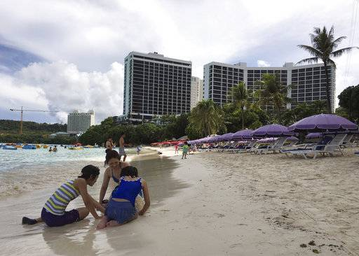 In this Thursday, Aug. 10, 2017, file photo, a family plays in the sand in Tumon, Guam. Threatening to fire a volley of missiles toward a major U.S. military hub _ and the home to 160,000 American civilians _ may seem like a pretty bad move for a country that is seriously outgunned and has an awful lot to lose. But pushing the envelope, or just threatening to do so, is what North Korea does best.