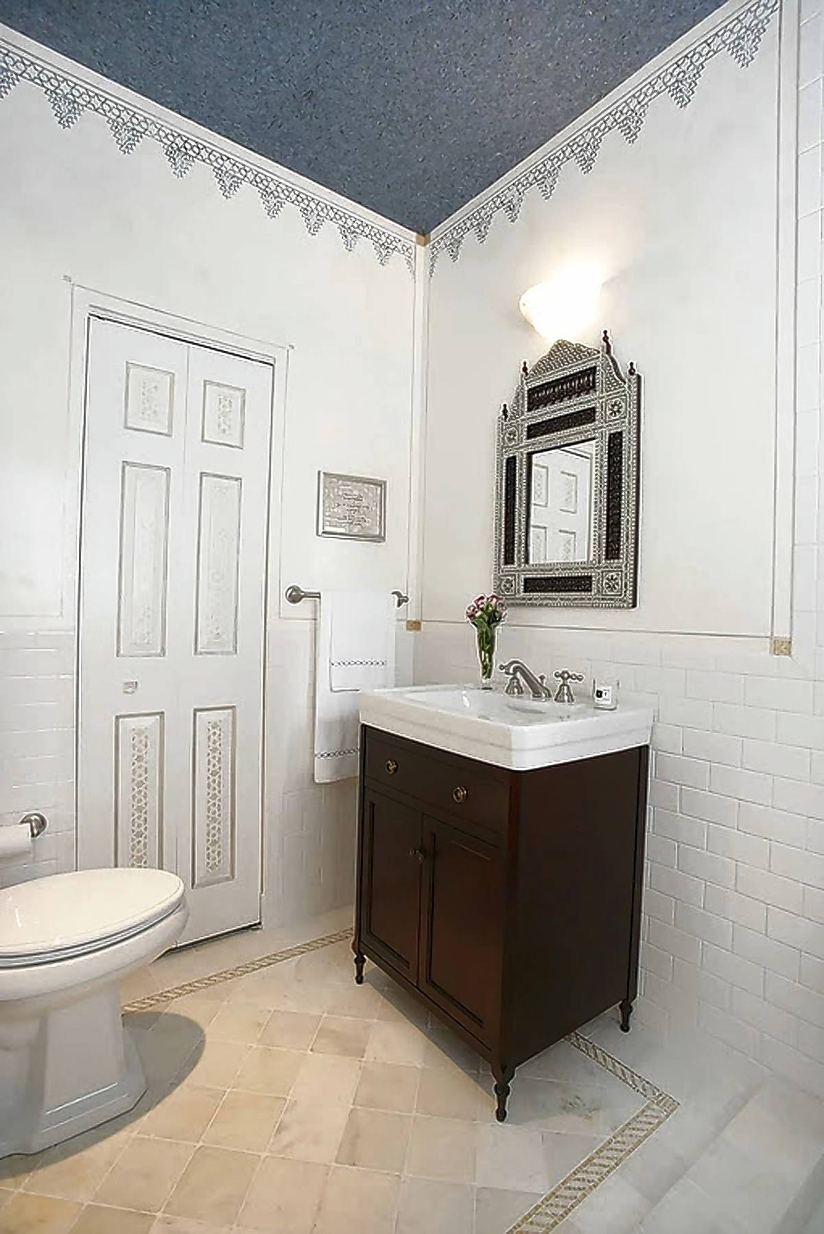 All-white bathrooms can be updated easily with a dash of color, wallpaper, lighting and accessories.