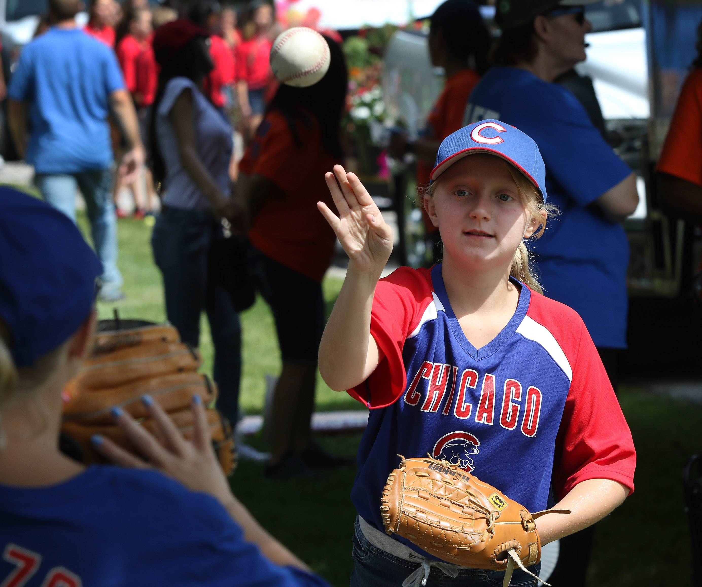 "Abi Harris, 11, of Gurnee plays catch with her twin sister, Skylar, before marching along Old Grand Avenue during the 2017 Gurnee Days Parade on Sunday. The theme of the parade was ""Let's Play Ball."""