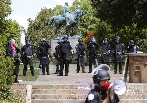 State Police in riot gear guard Lee Park after a white nationalist demonstration was declared illegal and the park was cleared in Charlottesville, Va., Saturday, Aug. 12, 2017.  Hundreds of people chanted, threw punches, hurled water bottles and unleashed chemical sprays on each other Saturday after violence erupted at the white nationalist rally.