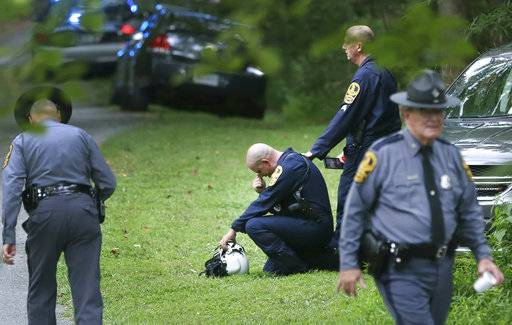 Authorities work near the scene of a deadly helicopter crash near Charlottesville, Va., on Saturday Aug. 12, 2017. (Shelby Lum/Richmond Times-Dispatch via AP)