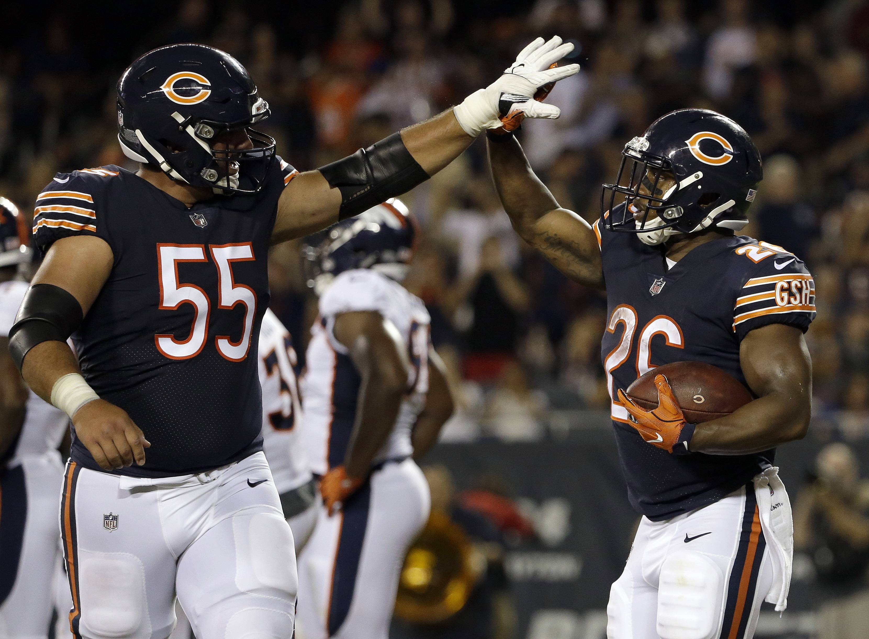 Chicago Bears running back Benny Cunningham (26) celebrates a touchdown with center Hroniss Grasu (55) during the second half of an NFL preseason football game against the Denver Broncos, Thursday, Aug. 10, 2017, in Chicago.