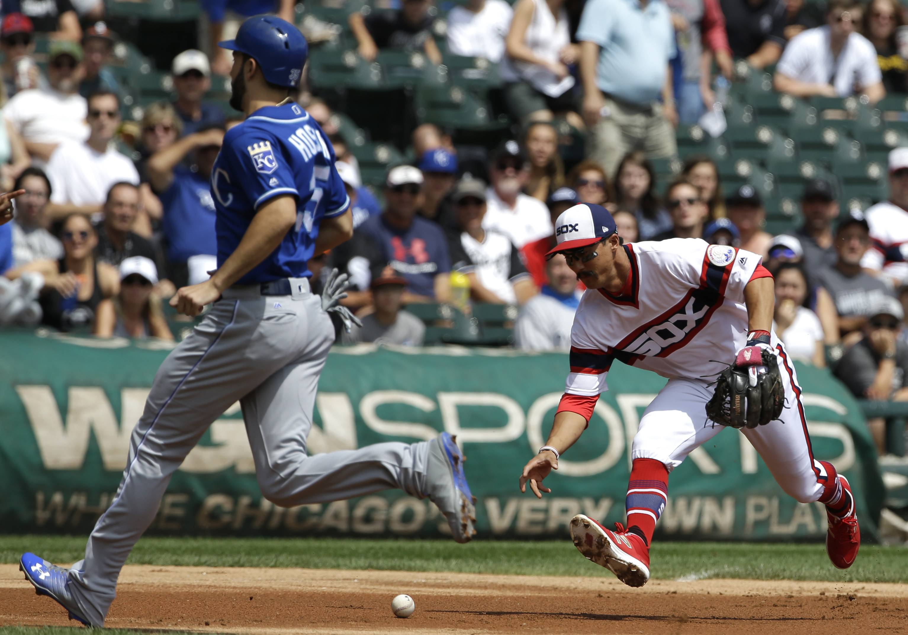 Chicago White Sox third baseman Tyler Saladino, right, makes a fielding error while trying to grab a ball hit by Kansas City Royals' Melky Cabrera as Eric Hosmer runs to third base during the first inning of a baseball game, Sunday, Aug. 13, 2017, in Chicago.