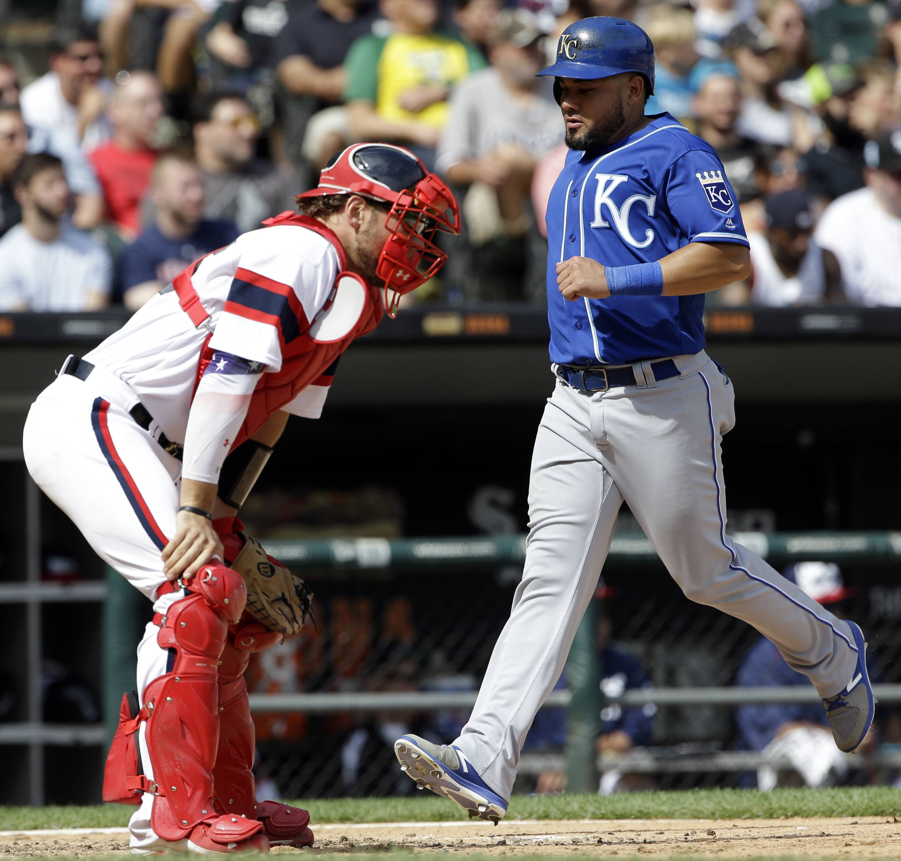 Kansas City Royals' Melky Cabrera, right, scores on a single by Jorge Bonifacio as Chicago White Sox catcher Kevan Smith looks to the field during the sixth inning of a baseball game Sunday, Aug. 13, 2017, in Chicago.