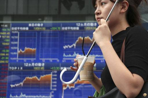 A woman walks past an electronic stock indicator of a securities firm in Tokyo, Monday, Aug. 14, 2017. Shares were mostly higher in Asia on Monday, although Japan's Nikkei 225 benchmark fell as tensions over North Korea kept the yen strong against the dollar. (AP Photo/Shizuo Kambayashi)