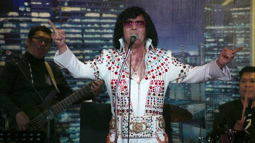 "In this Aug. 10, 2017, photo, Douglas Masuda, Elvis of Japan performs on stage in Manila, Philippines, for the ""Elvis Tribute Night: Young Once v.s. Young Ones"" event. Elvis Presley, crowned as the ""King of Rock and Roll,"" will be celebrating his 40th death anniversary this year. To pay tribute to the legend, the Elvis Presley Friendship Club, Philippines International has organized a special event that brings together both veteran and up-and-coming Elvis Tribute Artists. (AP Photo/Cecilia Forbes)"