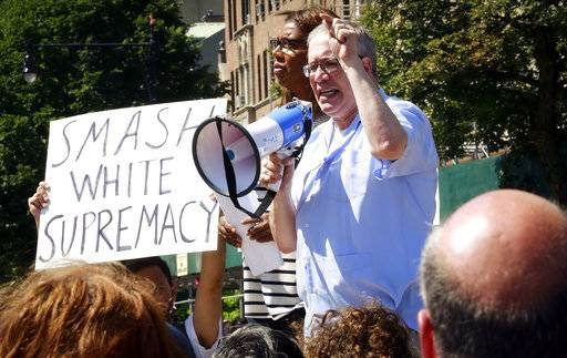 "City Advocate Letitia James, left, wait her turn to as City Comptroller Scott Stringer address protesters at a ""Peace and Sanity"" rally Sunday, Aug. 13, 2017, in the Brooklyn borough of New York, during a rally about white supremacy violence in Charlottesville, Va., (AP Photo/Bebeto Matthews)"