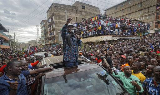 Kenyan opposition leader Raila Odinga gestures to thousands of supporters gathered in the Mathare area of Nairobi, Kenya Sunday, Aug. 13, 2017. Odinga on Sunday condemned police killings of rioters during protests after the country's disputed election and is urging supporters to skip work Monday. (AP Photo/Ben Curtis)
