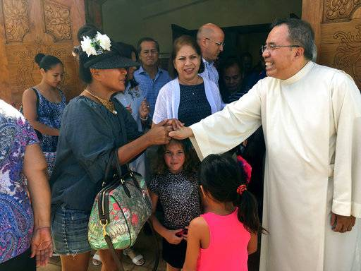 "Pastor Fr. Jose Antonio"" Lito"" P. Abad, right, greets parishioners as they leave Blessed Diego de San Vitores Church following Sunday Mass, Sunday, Aug. 13, 2017, in Tumon, Guam. Across Guam - where nearly everyone is Roman Catholic - priests are praying for peace as residents of the U.S. Pacific island territory face a missile threat from North Korea."