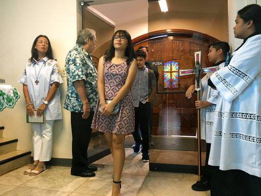 Locals arrive at Blessed Diego de San Vitores Church to attend Sunday Mass, Sunday, Aug. 13, 2017, in Tumon, Guam. Across Guam - where nearly everyone is Roman Catholic - priests are praying for peace as residents of the U.S. Pacific island territory face a missile threat from North Korea.
